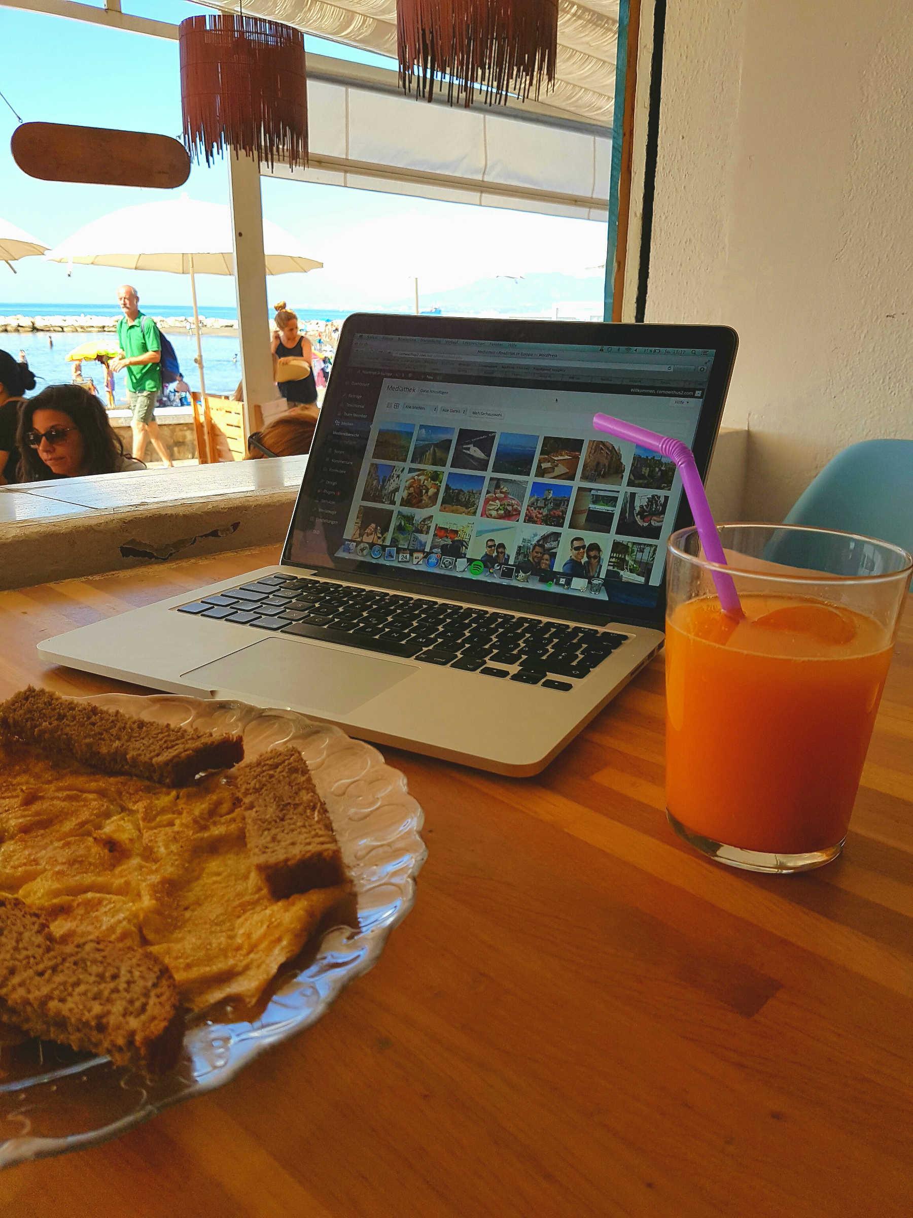 Laptop, Orangensaft, Rührei und Blick aufs Meer