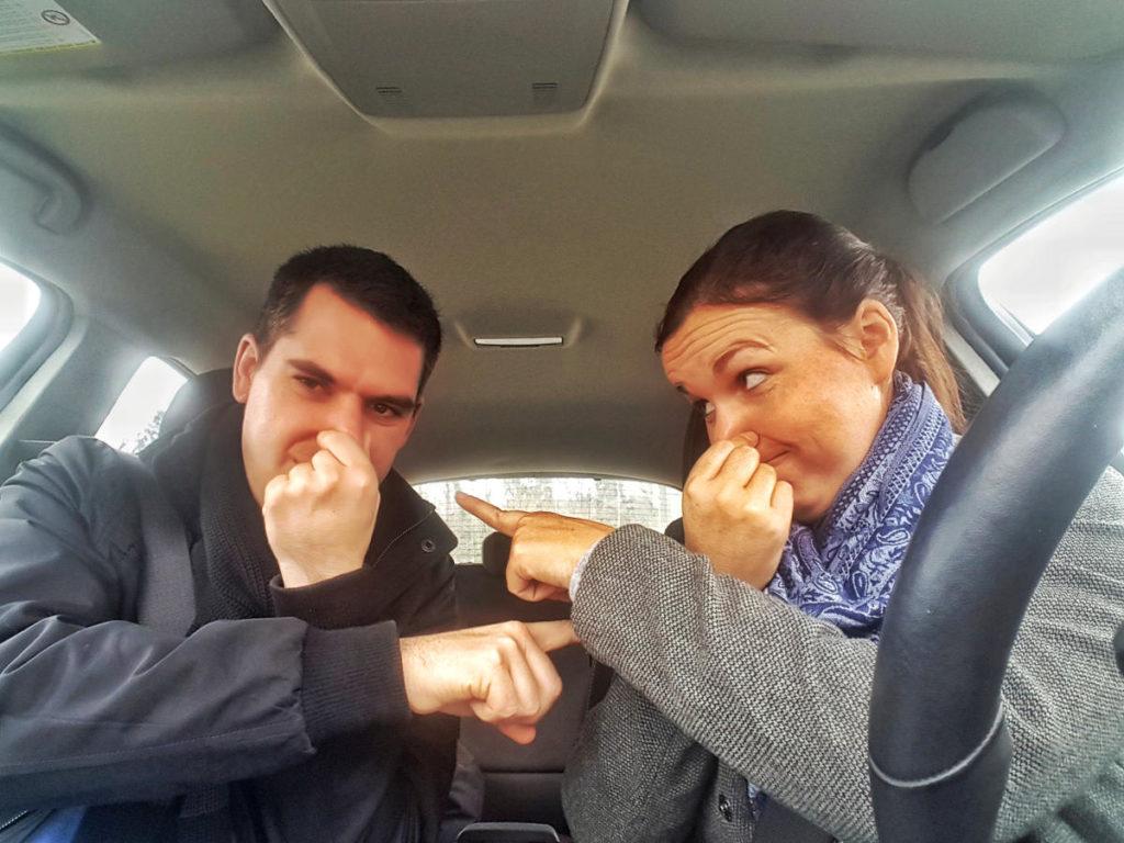 Steffi und Lui im Auto, Nase zuhaltend auf den anderen zeigend - mehr Spass Reisen im Auto