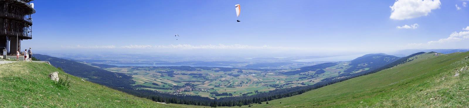 Panoramabild mit Gleitschirmfliegern, Blick auf Seen in Ebene - Wandern in der Schweiz / Kurztrip Schweiz