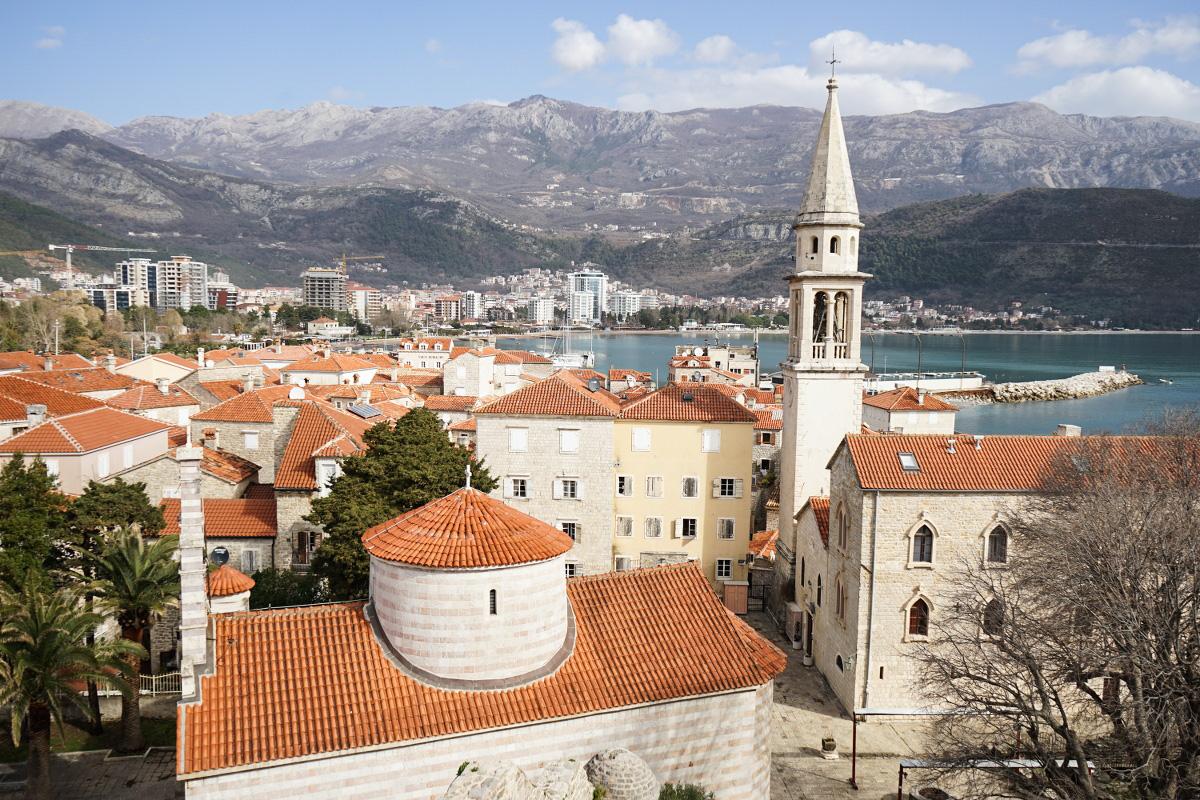 Altstadthäuser und Kirche, Bucht, moderne Hochhäuser im Hintergrund und Berge - Budva, Montenegro