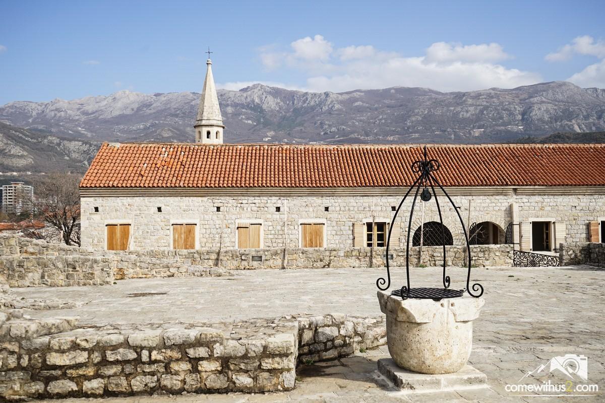 Brunnen, alte Gebäude, Kirchturm und Berge im Hintergrund, Budva