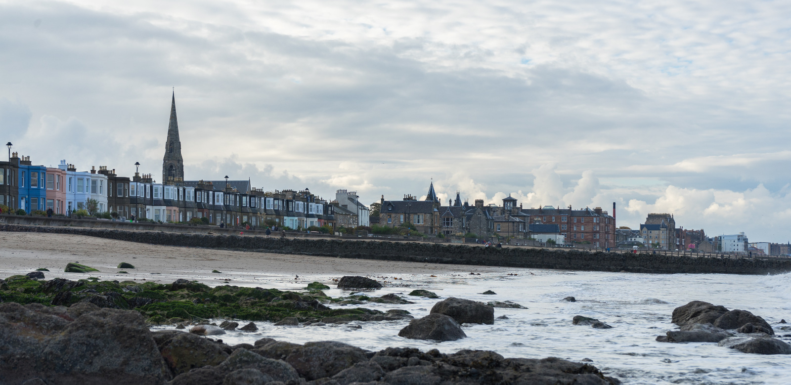 Blick über Fels-Strand zur Promenade - graue Wolken