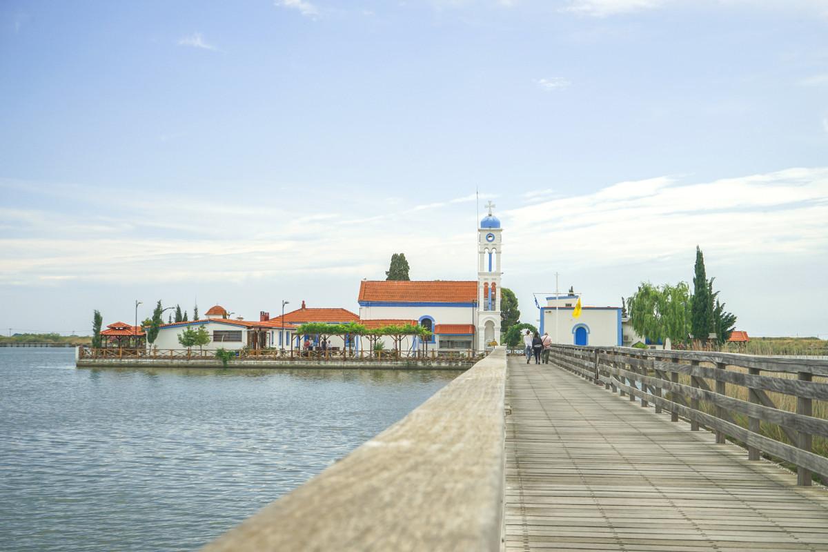 Holzsteg führt zu weiss-blauem kleinen Kloster auf Insel - Agios Nikolaos Porto Lagos