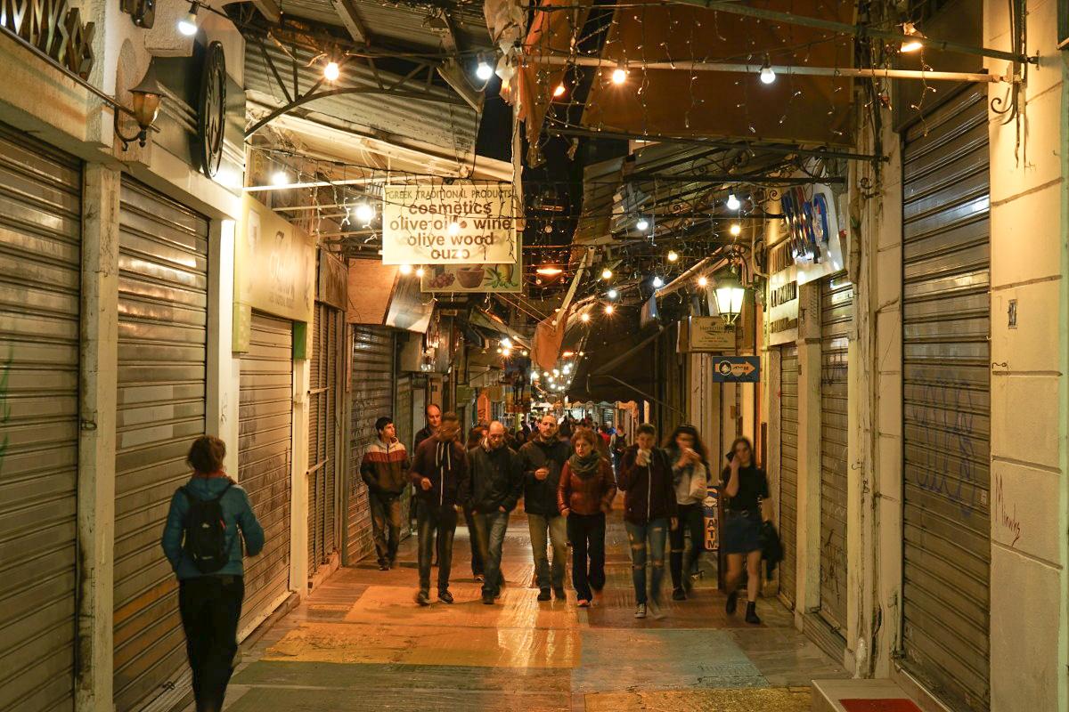 Junge Leute laufen durch Strasse, Athen bei Nacht