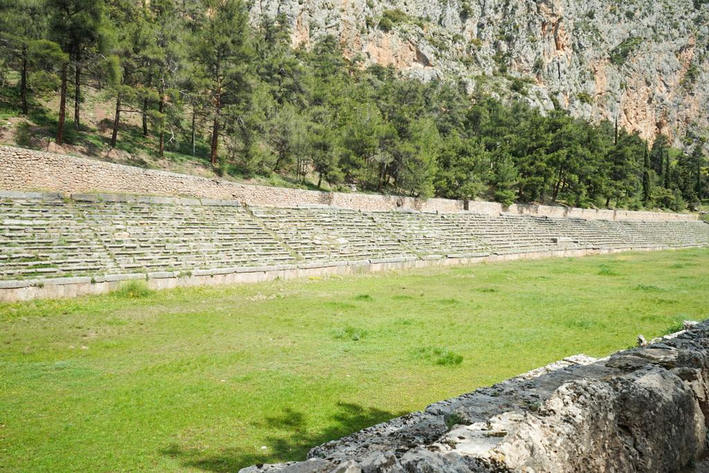 Langgezogene ebene Rasenfläche, darum steinerne Sitzbänke - Stadion Delphi Ruinenstadt