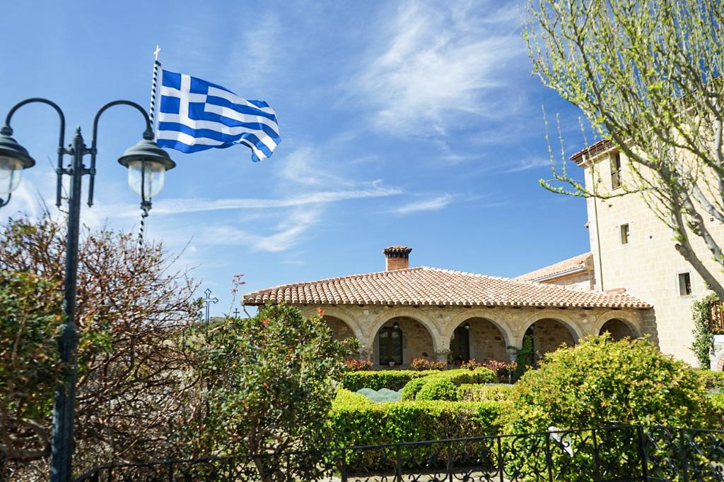 Geschwungene Torbögen, perfekt geschnittene Hecken, Griechenlandflagge - Meteora Klöster