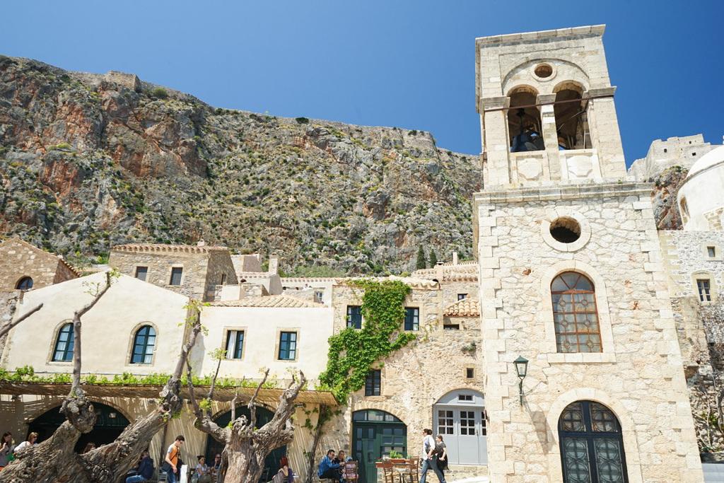 Steinerner Kirchturm und Häuser darum, Berg im Hintergrund - Monemvasia besichtigen