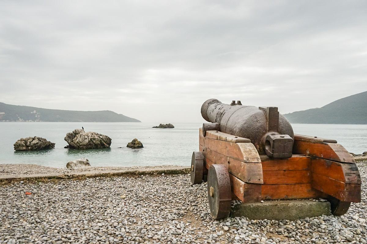 Kanone auf Holzwagen am Kiesstrand mit Blick aufs Meer - Herceg Novi - Montenegro