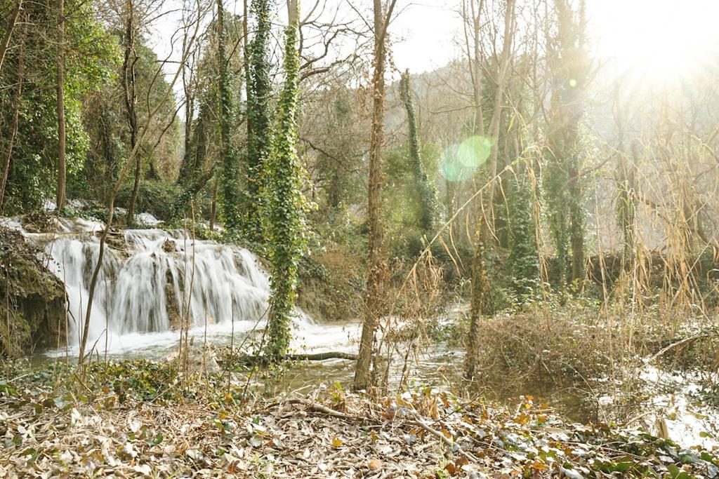 Mitten im Wald kleiner Wasserfall und Sonnenschein - Krka Nationalpark