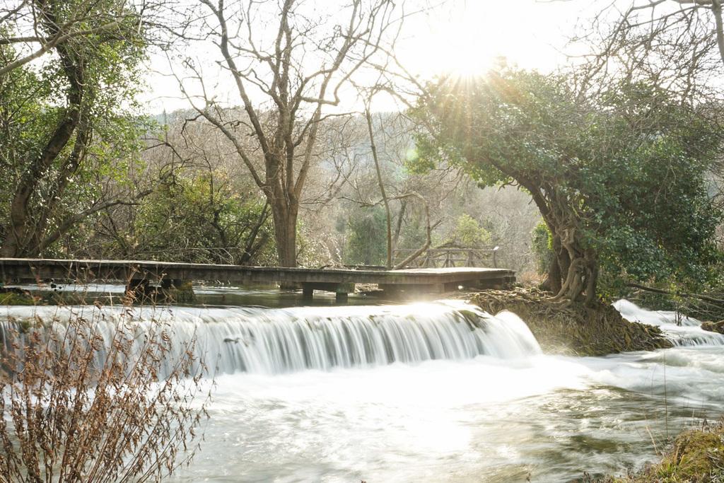 Steg, darunter fliesst Fluss über kleine Stufe - Krka Nationalpark