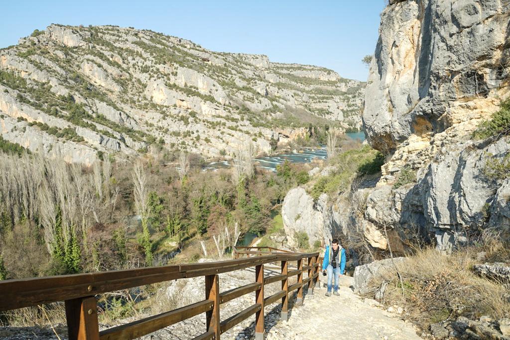 Lui steigt sehr steilen Fels hinauf, Geländer, Hintergrund Schlucht mit Fluss - Krka Nationalpark