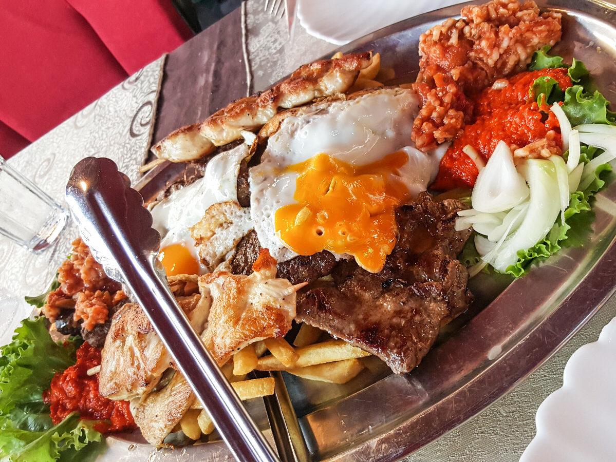 Platte mit verschiedenen Fleischstücken ,Pommes, Spiegelei und Ayvar-Dipp - Essen in Kroatien