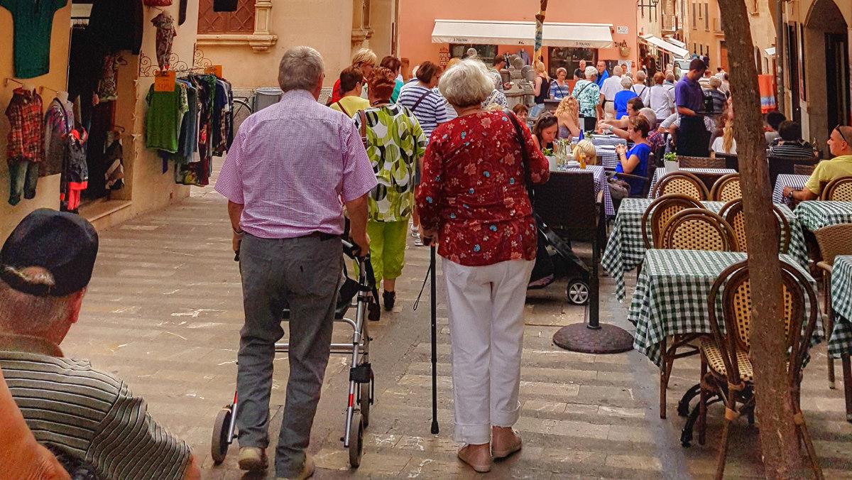 Mann mit Rollator und Dame mit Stock durch enge Gassen - Mallorca mit Senioren