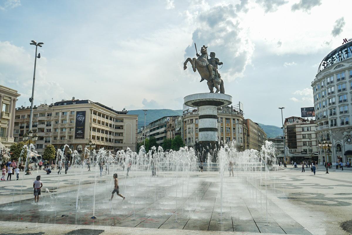 Reiterstatue auf Sockel mit Wasserspiel und Kindern davor. Sehenswürdigkeiten Skopje