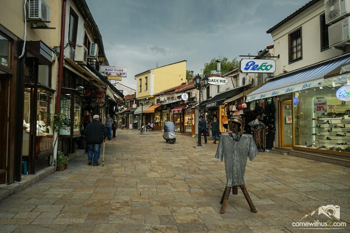 Fussgängerzone mit kleinen Geschäften, Ritterrüstung, pechschwarzer Himmel - Skopje besichtigen