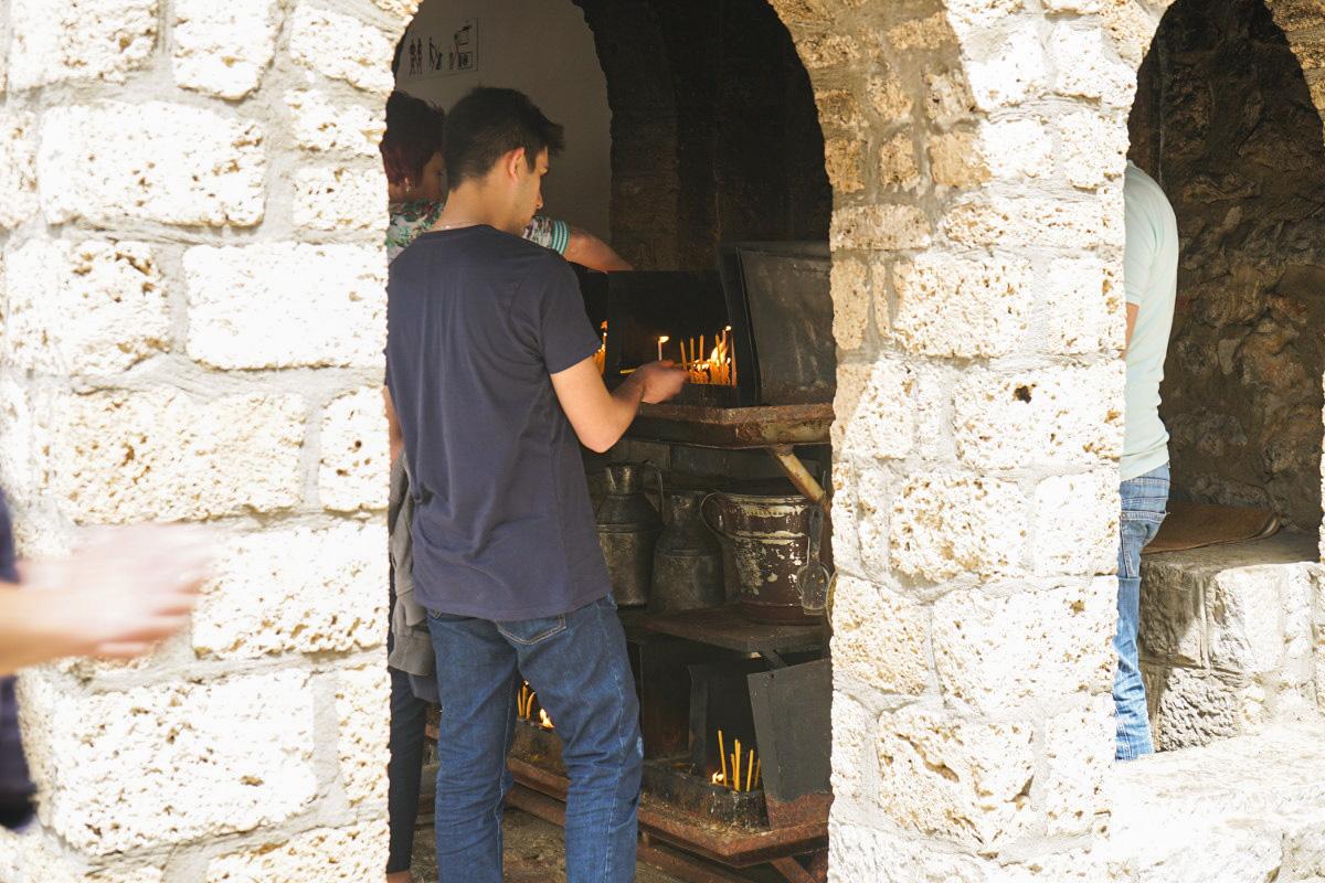 Gläubige zünden eine Kerze vor der Kirche an. Sveti Naum - Mazedonien Sehenswürdigkeiten