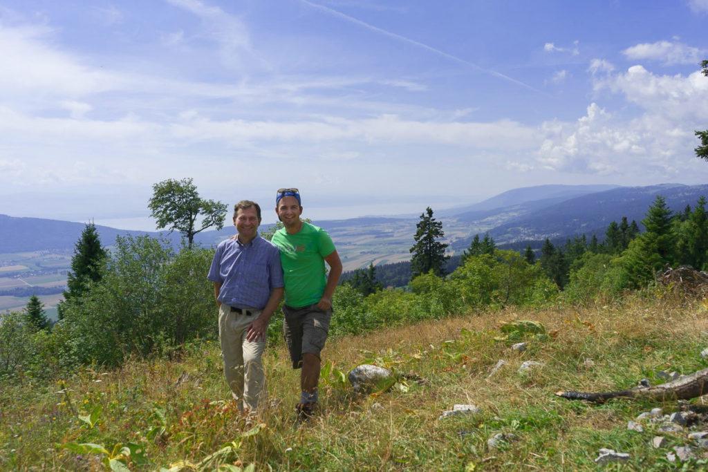 Vater und Sohn im Gras mit Blick ins weite Tal zu den Seen - Wandern in der Schweiz / Kurztrip Schweiz