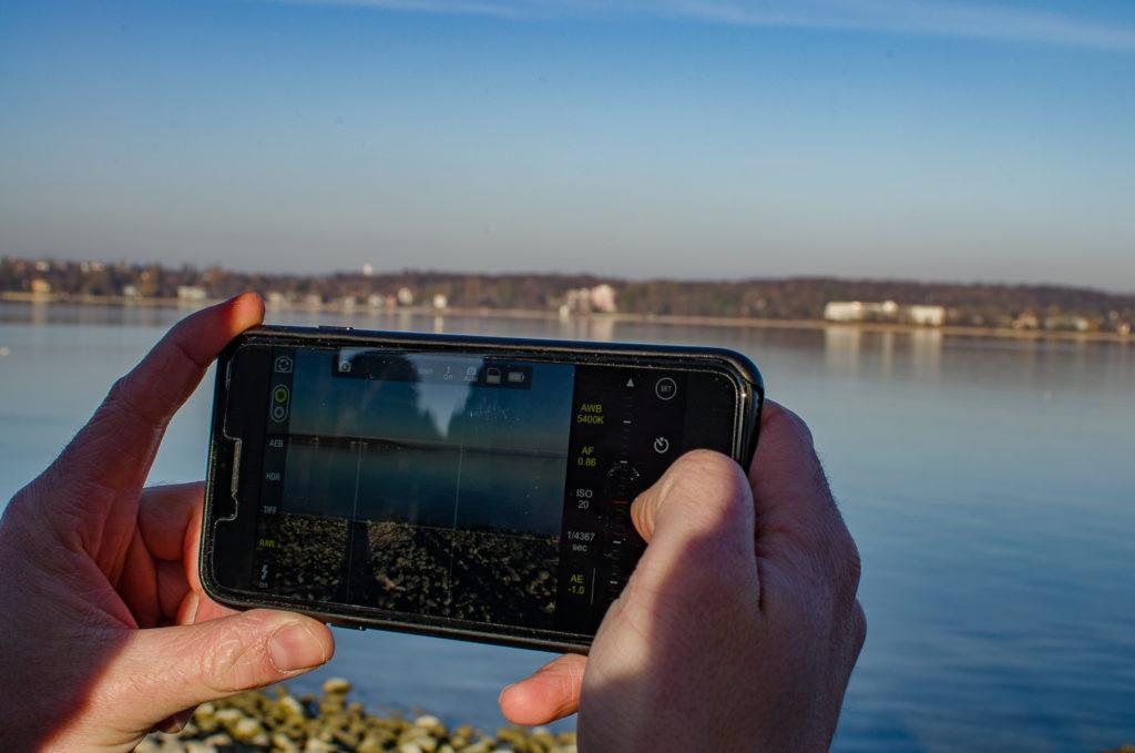 iPhone in den Händen mit Blick auf See & App auf Display