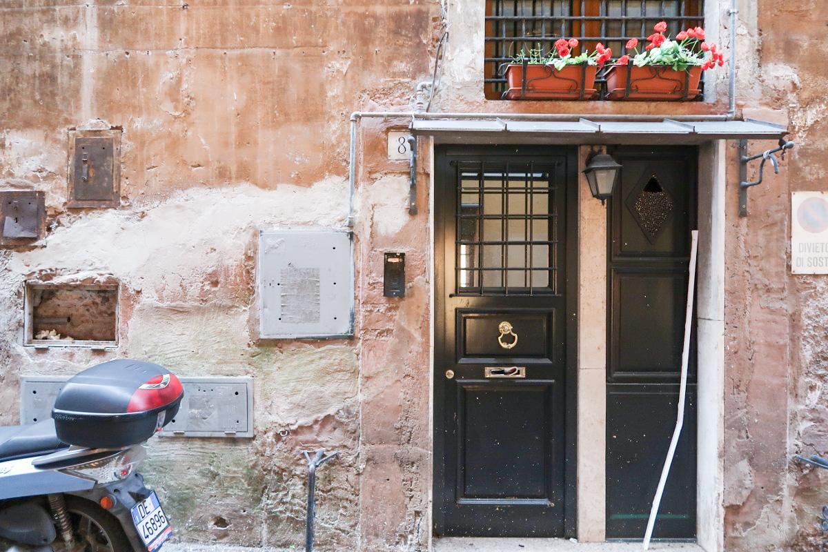 Türe, verfärbte Wand, Blumen und Moped - Rom besichtigen
