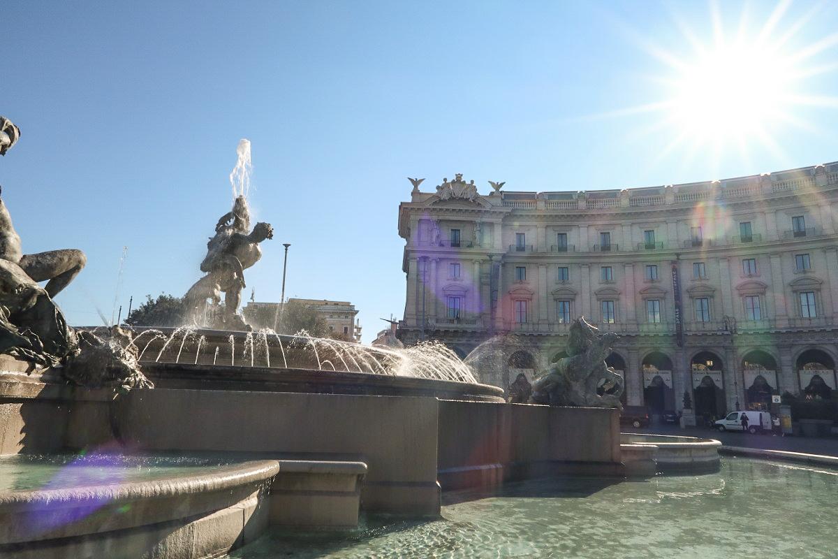Brunnen, dahinter hohe Häuser, blauer Himmel und Sonnenschein - Rom besichtigen