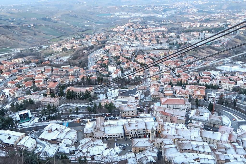 Häuser mit roten Dächern, Seilbahn-Seile führen durch Bild - Reisen nach San Marino