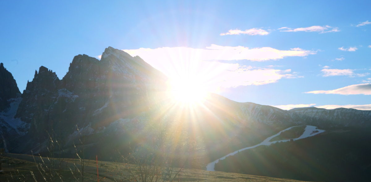 Sonne scheint hitner Berg hervor, blauer Himmel