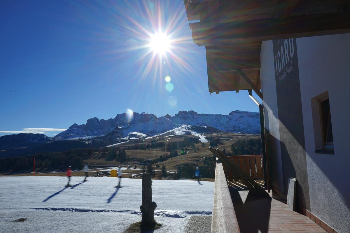 Hotel, Skipiste mit Skifahrern, blauer Himmel und Sonnenschein