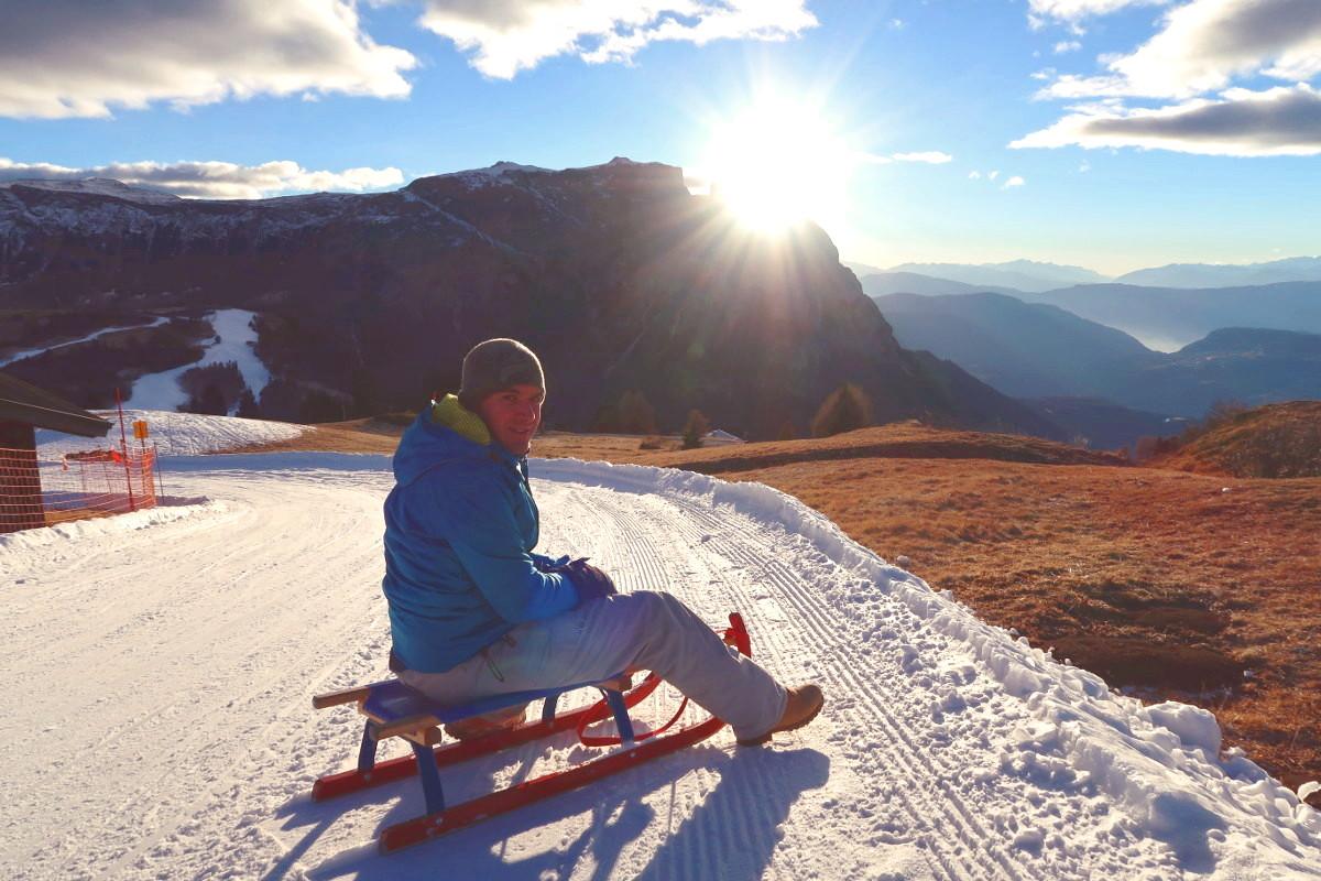 Lui auf Rodel dahinter Berge mit Sonne -Südtirol, Seiser Alm, Dolomiten