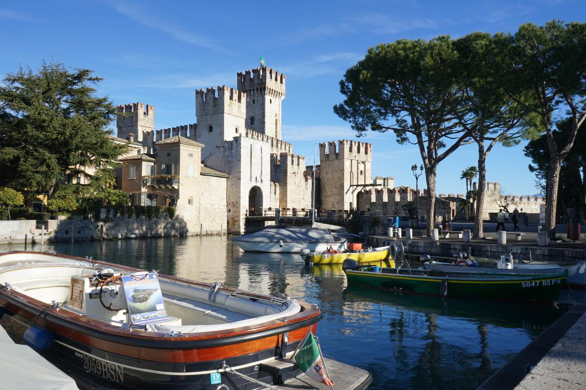 Burg, davor Kanal mit Booten