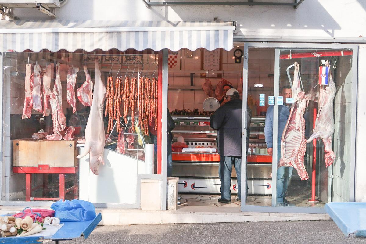 zwei Schweinehälften, Würste und mehr hängen da - Sehenswürdigkeiten Split