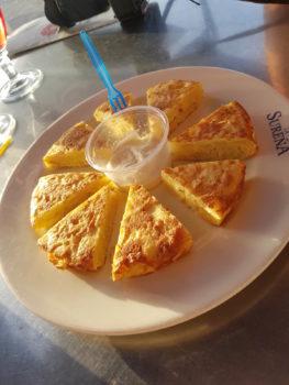Rundes Omlett in Ecken geschnitten und um eine Sauce in der Mitte verteilt - Tapas essen Spanien