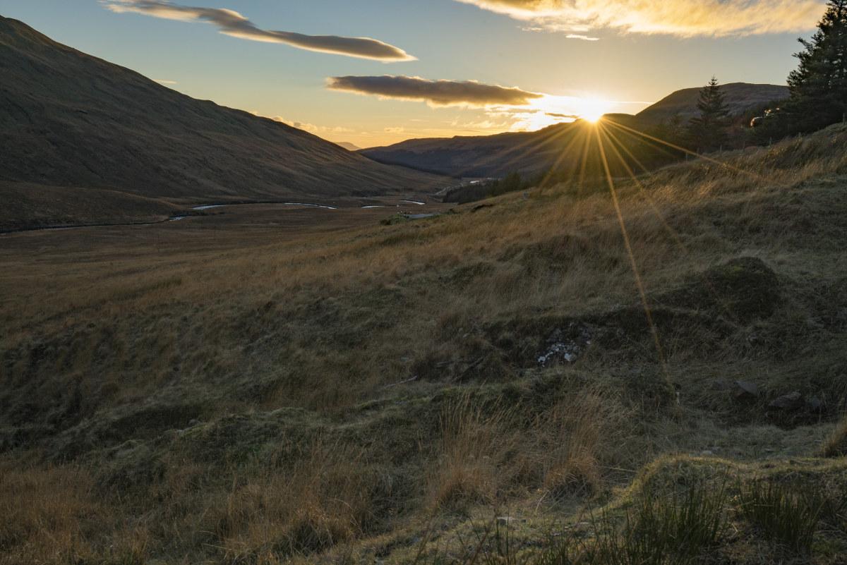 Letzte Sonnenstrahlen, Sonne hinter Berg, gelbliches Grasland - goldene Stunde