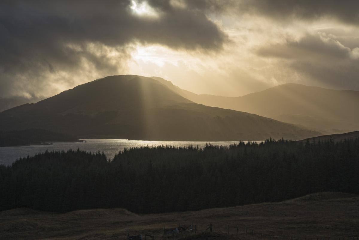 Sonnenstrahlen dringen durch Wolken auf Hügellandschaft