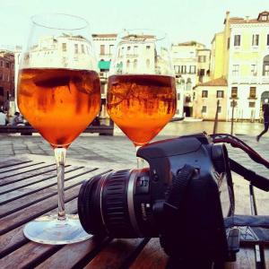 Apero und Kamera auf Tisch, Hintergrund Kulisse Venedigs