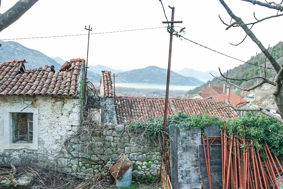 heruntergekommenes Steinhaus, über dem Dach See und Hügel zu sehen - Wandern in Montenegro, Virpazar, Skradar See