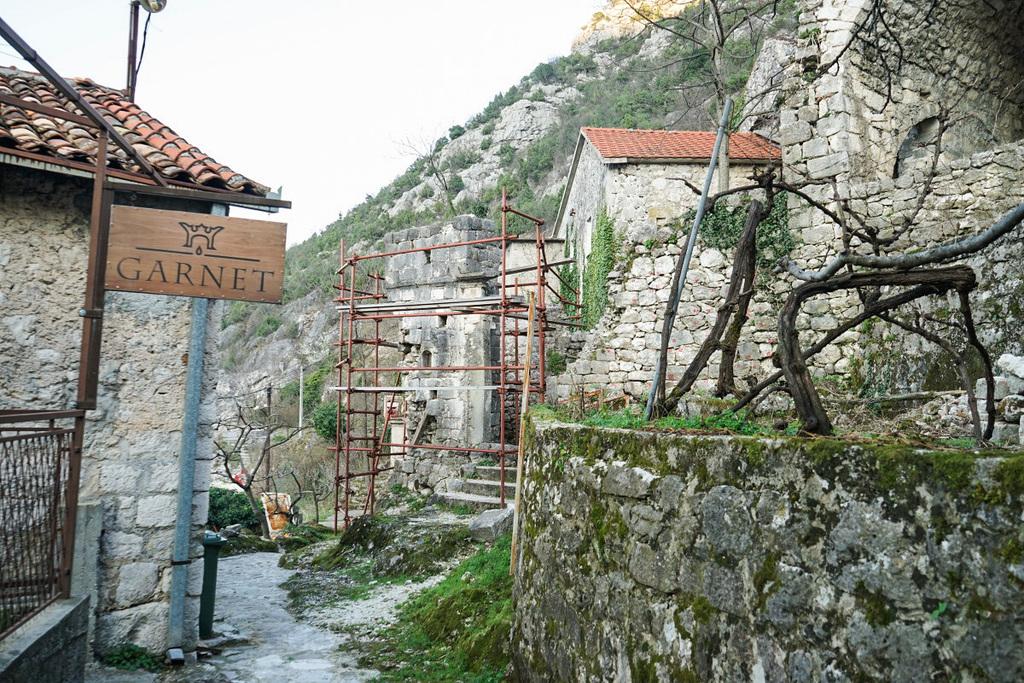 Gerüst vor Stteinmauer, Schild Garnet - Wandern in Montenegro, Virpazar, Skradar See
