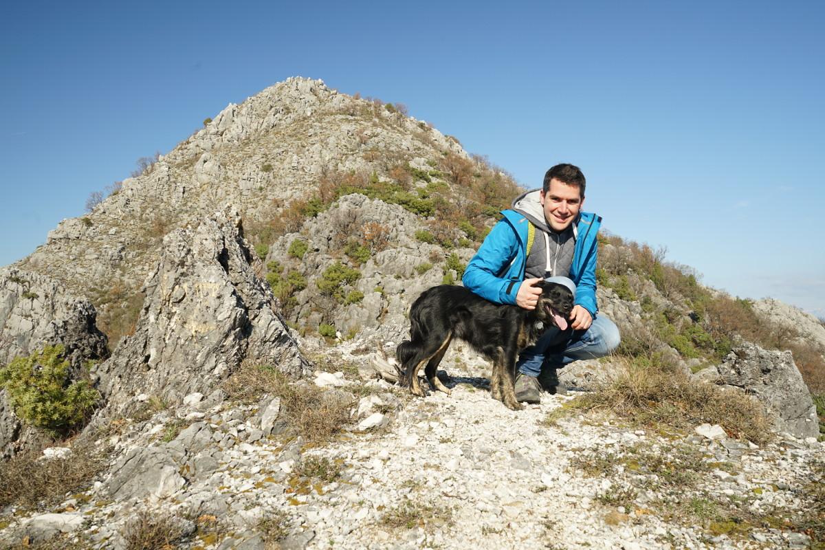 Bergspitze im Hintergrund, davor Lui knieend mit schwarzem Hund - Wandern in Montenegro, Virpazar, Skradar See
