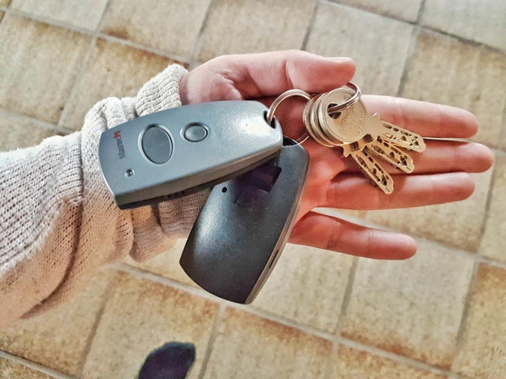 Hausschlüssel und Garagensensor auf Hand - Reisevorbereitung