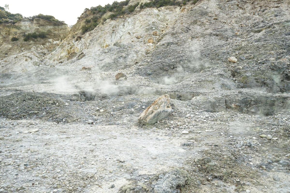 Steinhang mit kleinen Dampfschwaden - Vulkan Solfatara besichtigen