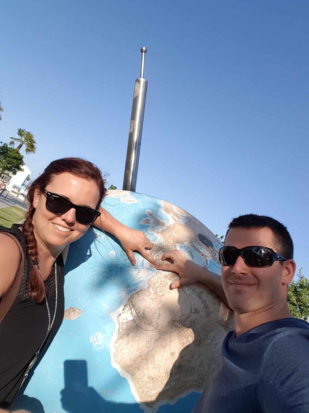 Steffi & Lui vor einer Weltkugel mit Finger auf Südspanien