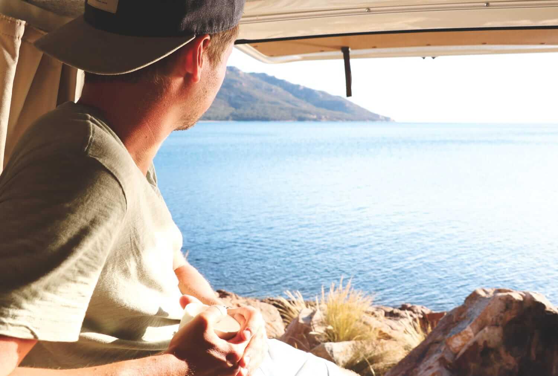 Daniel blickt aufs Meer aus dem Camper